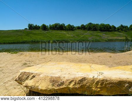 Lake Beach With Big Flat Stone. Countryside Landscape With Sunny Sky. Travel Destination And Fishing