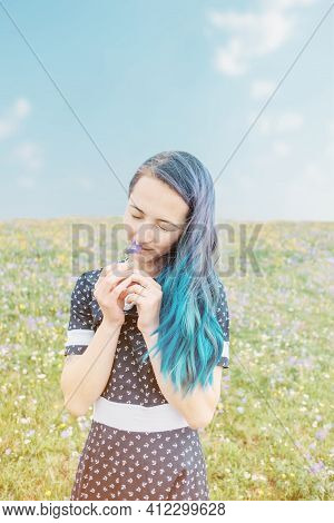 Beautiful Young Woman Standing In Meadow And Sniffing A Bellflower In Summer Outdoor.