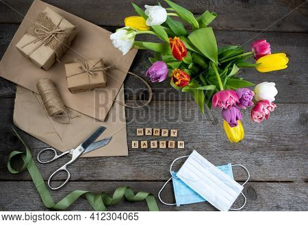 Phrase Happy Easter. Gift Wrapping For The Holiday. Bouquet Of Tulips On A Wooden Background. Medica