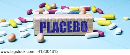 A Wooden Block With The Word Placebo Stands On A Blue Background Among Multi-colored Pills. Medical