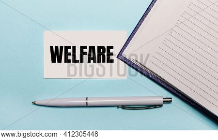 On A Light Blue Background, An Open Notebook, A White Pen And A Card With The Text Welfare. View Fro