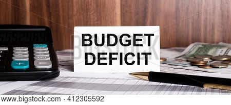 On A Wooden Background Lies Pen With Calculator And White Card With Words Budget Deficit