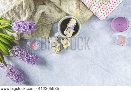 Cup Of Coffee With Milk And Delicious Fried Marshmallow And Pink Hyacinths On Light Concrete Surface