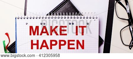 The Words Make It Happen Is Written In Red In A White Notebook Next To Black-framed Glasses.