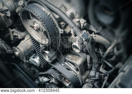 Replacement Timing Belt With Rollers On The Old Diesel Engine In A Car Service. Close Up. Blur Effec