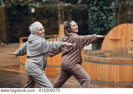 Women Doing Exercises Sports And Fitness Outdoors. Young And Senior Elderly Woman Warming Up And Yog