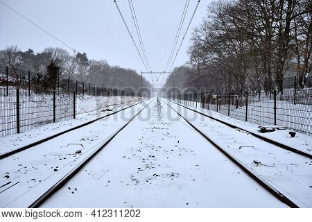 Railway Tracks During Snowfall In The Netherlands. Train Tracks Covered With Snow In A Snow Shower N