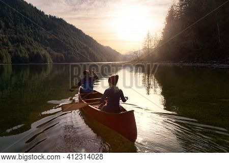 Couple Friends Canoeing On A Wooden Canoe During A Colorful Sunny Sunset. Cloudy Sky Artistic Render