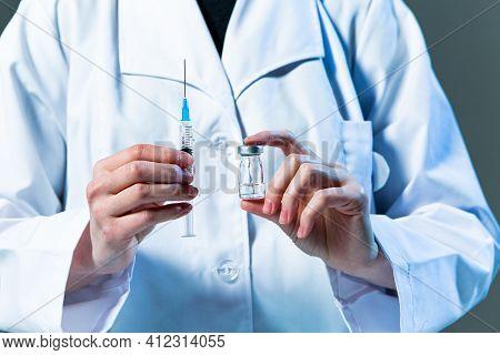 Close Up Of Coronavirus Vaccine Or Medicine Ampule, Syringe In Doctor Hands For Immune. Vaccination