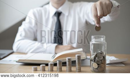 Financial Businessman With Coins Put In A Jar, Saving Money For Future Growth And Knowing How To Man