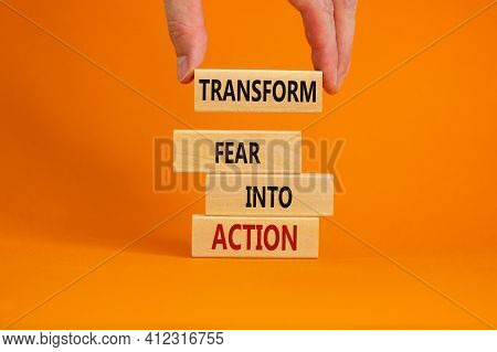 Transform Fear Into Action Symbol. Businessman Holds Wooden Blocks With Words 'transform Fear Into A