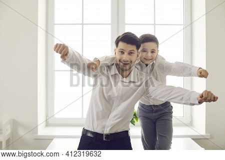 Happy Family Of Father And Son Having Fun At Home Making An Imaginary Flight On Camera.
