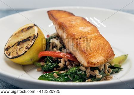 Pan Roasted Salmon Seasoned Perfectly On Top A Pile Of Barley And Garnished With Grilled Lemon Slice