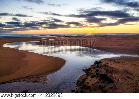 Raudasandur Pink Beach Iceland During Sunset With Mirrored Tributary In The Foreground