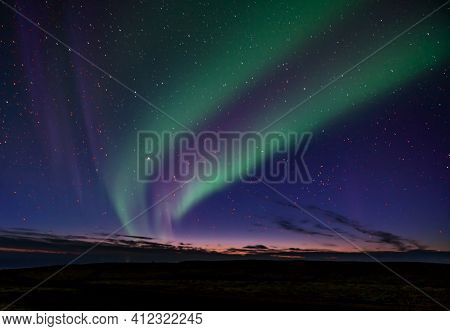 Double Band Northern Lights In Iceland. Rocky Foreground With The Last Glimmer Of Sun On The Horizon