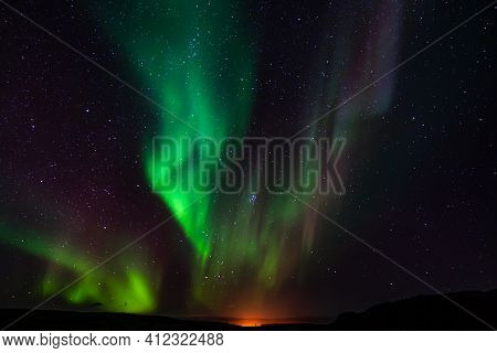 Colorful Northern Lights Dance Above The Glow Of The Setting Sun