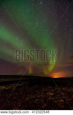 Triple Banded Northern Lights In A Smooth Bend Across The Rocky Horizon. The Last Glow Of Sunlight S