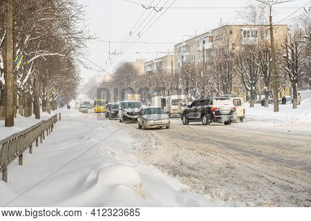 Lutsk, Ukraine - February 12,2020: Stuck Car In Snow And Ice. City Street After Blizzard. Buried Veh