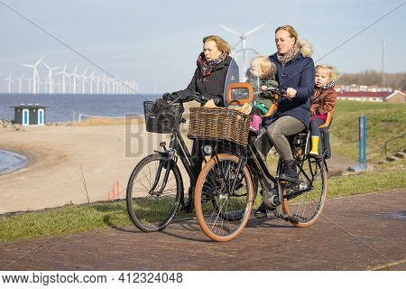 Urk, The Netherlands - February 19 2021: Women With Little Kids At Bycycle Near Dutch Coast Of Urk,