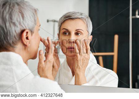 Mature Woman Applying Moisturizer In Bathroom. Senior Female In Bathrobe Doing Skincare