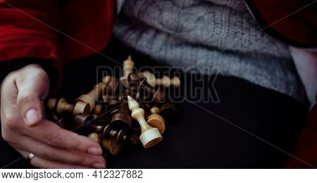 Close Up Of Chess Pieces On Legs Of Unrecognizable Woman. Unknown Female Holds Figures Of Chess On H