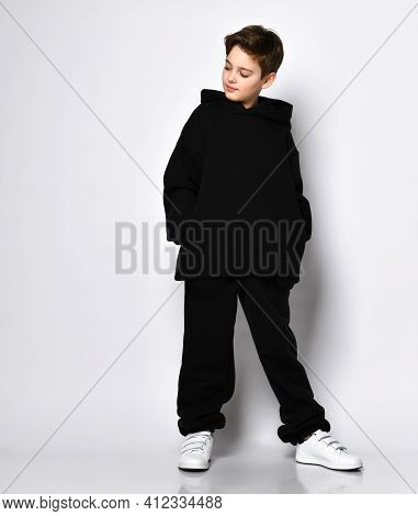 Cute Stylish Kid In Colourful Sportsuit Standing With Hood Over Head Pointing Fingers At Camera. Fas