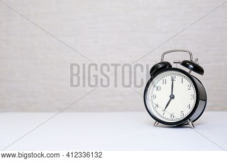 An Alarm Clock Showing 7 Oclock Standing On A White Table With Copy Space, Everyday Shedule And Morn