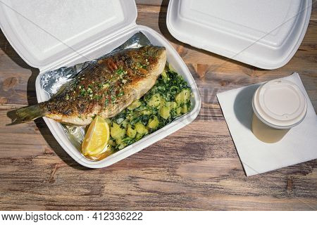Food Delivery. Grilled Fish ( Sea Bream ) With Green Leafy Vegetables And Slice Of Lemon In Takeout