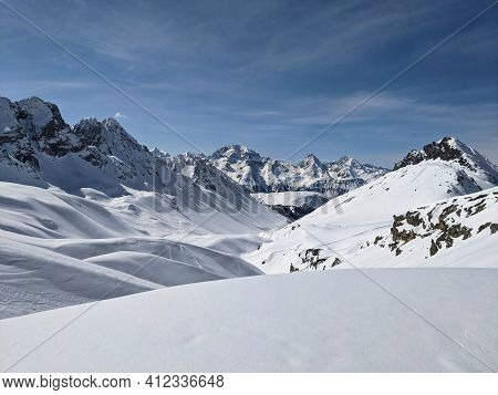 Panorama Of The Climber On The Snow Capped Mountain Range. Ducan Glacier In Switzerland. Freeride In