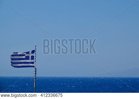 The Greek Flag And The Aegean Sea In The Background