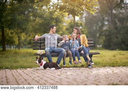 kids eating ice cream, enjoying with their parents smiling, sitting on a bench in park