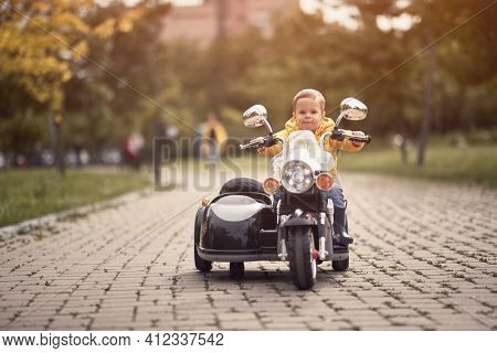 caucasian toddler driving replica of motorcycle outdoor in a park