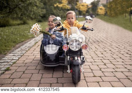 cute toddler driving little girl in sidecar of motorcycle toy on battery in park