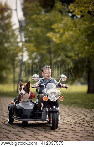 cute little boy enjoying in autumn park, driving electrical motorcycle toy with sidecar and his dog in it