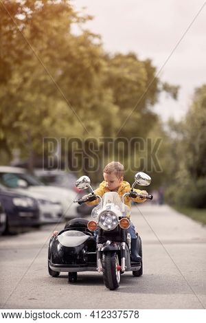 caucasian toddler sitting on a replica of motorcycle. electrical toy