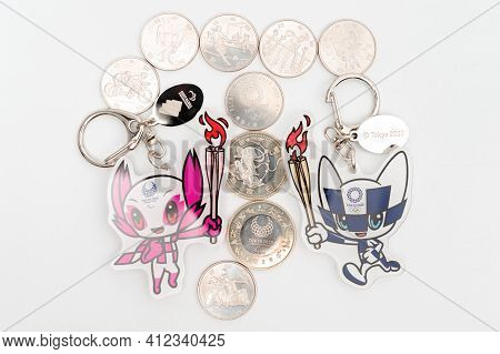 Tokyo, Japan - January 4, 2021: Mascot Keychains And Commemorative Coins Of 100 Yen And 500 Yen For