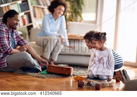 Kids riding skateboard on the floor and enjoying the playtime with their parents in a cheerful atmosphere at home. Family, together, love, playtime