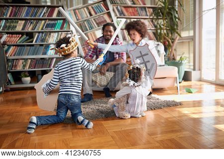 Mom and her son playing with swords and enjoying a playtime with family in a cheerful atmosphere at home. Family, together, love, playtime