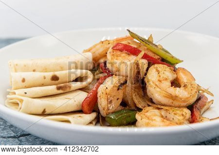 Jumbo Pieces Of Fajita Style Shrimp Piled On Stir Fry Vegetables Combined With Folded Tortillas To E