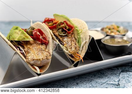 Pair Of Grilled Fish Tacos Loaded With Fillings And Topped With Fresh Avocado Wedges.