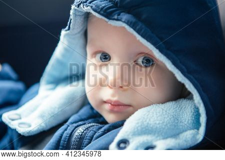 Cute Caucasian Baby Infant Sitting In Car Seat. Adorable Kid In Outwear Clothes In Automobile Vehicl