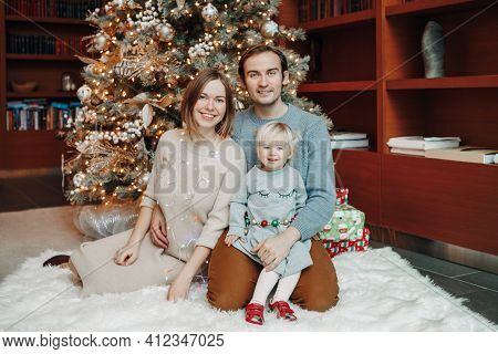 Smiling Caucasian Mother And Father With Baby Girl Sitting Together By Decorated Christmas Tree. Hap