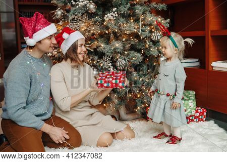 Smiling Caucasian Mother And Father Giving Baby Girl Christmas Gift Present Box. Happy Family Celebr