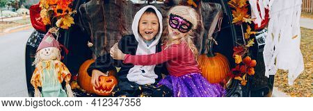 Trick Or Trunk. Children Celebrating Halloween In Trunk Of Car. Boy And Girl Friends Celebrating Oct