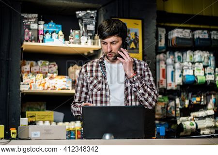 Bike Shop Owner At Work. Store Employee Takes An Order By Mobile Phone At Table Near Laptop In Trave