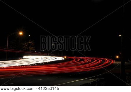 Red And White Car Light Trails At Night Curving Around The Corner In A Bend In The At Night In The D