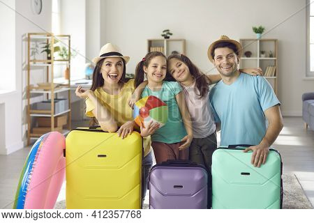 Portrait Of Happy Smiling Family With Their Packed Suitcases Ready For Holiday Trip