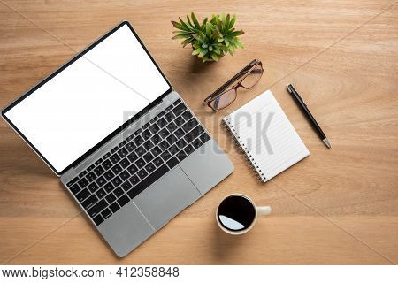 Laptop Computer With Blank Mock Up Screen Is On Top Wooden Office Desk Table With Cup Of Black Coffe