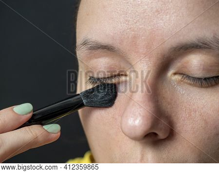 Close-up Of A Woman Applying A Brush Shadow On The Eyelids. Make-up At Home, Beauty