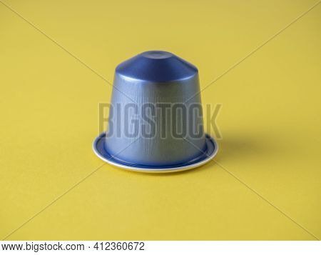 One Blue Coffee Capsule With Aromatic Italian Coffee On A Yellow Background. Close-up, Front View, C